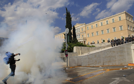 A protester throws back a tear gas canister at policemen in front of the parliament during violent protests in Athens' Syntagma square